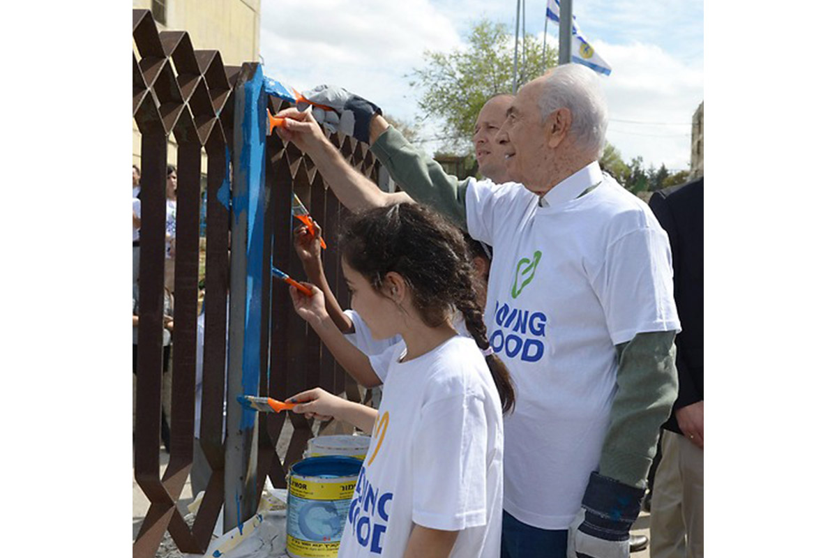 President Peres painting on Good Deeds Day (photo credit: Mark Neiman, GPO)