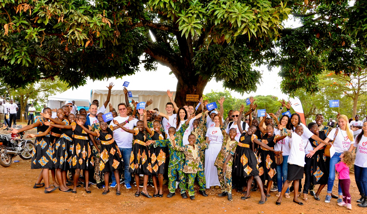 Volunteers and kids from Conord Roy Muasasko in Uganda smile with happiness.